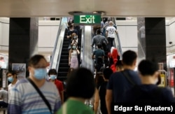 Commuters wearing protective face masks leave a train station during the coronavirus disease (COVID-19) outbreak in Singapore August 17, 2020.