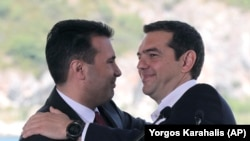 GREECE -- Greek Prime Minister Alexis Tsipras, right and his Macedonian counterpart Zoran Zaev, embrace during a signing of an agreement for Macedonia's new name in the village of Psarades, June 17, 2018