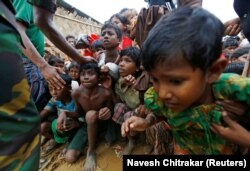 Rohingya refugee children struggle as they wait to receive food outside the distribution center at Palong Khali refugee camp near Cox's Bazar, Bangladesh, on Nov. 17, 2017.