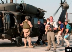 Iraq -- US administrator Paul Bremer (C) is guarded by private US security company personnel while he boarded a helicopter in the Iraqi city of Hillah, June 17, 2007