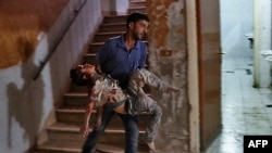 Syria -- A Syrian man carries a severely wounded boy at a make-shift hospital in the rebel-held town of Douma, east of the capital Damascus, following reported cluster bomb shelling, October 20, 2016