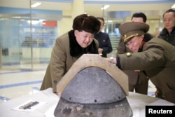 North Korean leader Kim Jong Un examiners a warhead tip of a ballistic missile after an alleged simulated test of the missile's atmospheric re-entry capability, March 15, 2016.