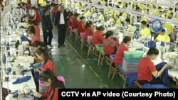 CHINA – In this file image from undated video footage run by China's CCTV, Muslim trainees work in a garment factory at the Hotan Vocational Education and Training Center in Hotan, Xinjiang.