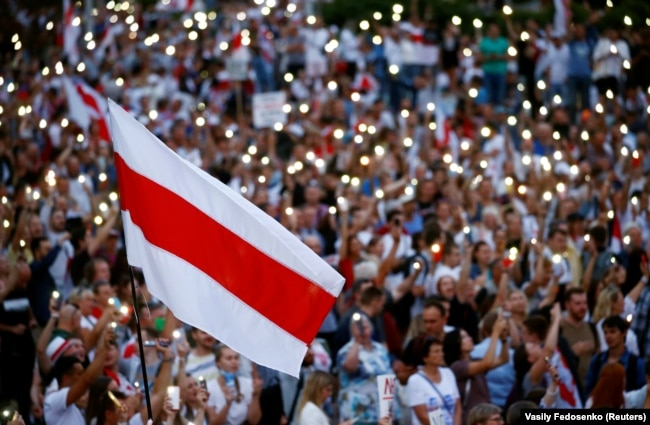 Minsk, Belarus - A historical white-red-white flag of Belarus is seen as people attend an opposition demonstration to protest against presidential election results