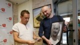 UKRAINE -- Russian dissident journalist Arkady Babchenko (R) holds his portrait while listening to deputy chief of the Crimean Tatar channel ATR Aider Muzhdabayev at the office of the channel in Kyiv, May 31, 2018