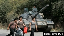GEORGIA -- Georgian refugees are seen walking past a Russian armoured vehicle in the village of Igoeti, 50 kilometers (31 miles) from Tbilisi, August 16, 2008