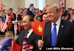 Former U.S. President Donald Trump and then Vietnamese Prime Minister Nguyen Xuan Phuc hold flags as they are greeted by students during their meeting at the Office of Government Hall in Hanoi, on Feb 27, 2019.