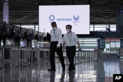 Staffs wearing protective masks to help curb the spread of the coronavirus walk in the empty ticketing area at Narita International Airport in Narita, Japan, on Tuesday, June 1, 2021.