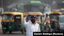 A traffic policeman wears a mask to protect himself from air pollution at a junction during restrictions on private vehicles based on registration plates, on a smoggy morning in New Delhi, India, November 4, 2019. REUTERS/Danish Siddiqui