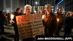 """Woman holds up sign rejecting a """"health dictatorship, the withdrawal of fundamental rights, state supervision, compulsory vaccination and wearing of masks"""" during a demonstration against the German government's current measures to curb the spread of COVID-19, on November 7, 2020."""