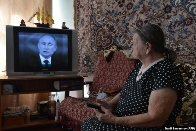 Russia -- An elderly woman watches TV broadcasting of Russian President Vladimir Putin's annual televised question-and-answer session with the nation in the southern city of Stavropol, April 17, 2018