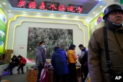 "Visitors look at a booth near the words ""Xinjiang is a good place"" during the 11th Xinjiang Agricultural Produce Beijing Fair held in Beijing on Saturday, Dec. 5, 2020. (AP Photo/Ng Han Guan)"
