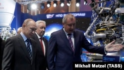 RUSSIA -- Russian President Vladimir Putin and Roskosmos head Dmitry Rogozin (right) visit the state company that produces Proton rocket engines, in Moscow, April 12, 2019.