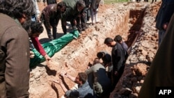 Syria -- Syrians dig a grave to bury the bodies of victims of a a suspected toxic gas attack in Khan Sheikhun, a nearby rebel-held town in Syria's northwestern Idlib province, April 5, 2017