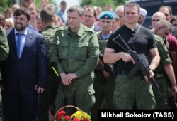 "UKRAINE – Alexander Zakharchenko (C), head of the Donetsk People's Republic (DPR), and Denis Pushilin (L), representative of ""DPR"", attends the commemorative events in memory of the people, who died during the Malaysia Airlines Boeing 777 crash on 17 July"