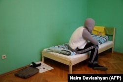 A Chechen man who fled persecution in his home republic for his sexual-orientation sits on his bed in Moscow on April 17, 2017.