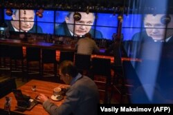 RUSSIA -- A man drinks a coffee in front of screens broadcasting Russian President Vladimir Putin's annual press conference, at a bar in Moscow, December 20, 2018.