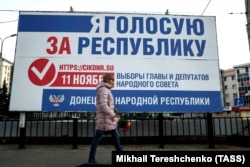 UKRAINE -- A woman walks past an election campaign billboard for elections in areas of eastern Ukraine held by Russia-backed separatists, on a street in Donetsk, November 7, 2018.