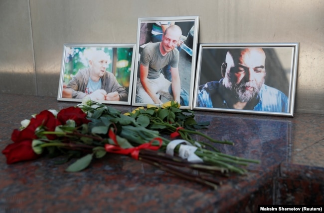 RUSSIA -- Photographs of journalists, (Right to left) Orhan Dzhemal, Kirill Radchenko and Aleksandr Rastorguyev, who were recently killed in Central African Republic by unidentified assailants, are on display outside the Central House of Journalists in Moscow, Augu