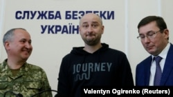 UKRAINE - Russian journalist Arkady Babchenko (C), who was reported murdered in the Ukrainian capital on May 29, Ukrainian Prosecutor General Yuriy Lutsenko (R) and head of the state security service (SBU) Vasily Gritsak attend a news briefing in Kyiv, Uk
