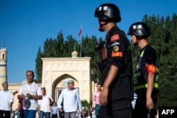 This picture taken on June 26, 2017 shows police patrolling as Muslims leave the Id Kah Mosque after the morning prayer on Eid al-Fitr in the old town of Kashgar in China's Xinjiang Uighur Autonomous Region.