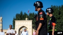 CHINA – Police patrolling as Muslims leave the Id Kah Mosque after the morning prayer on Eid al-Fitr in the old town of Kashgar in China's Xinjiang Uighur Autonomous Region, on June 26, 2017.
