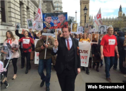 "Adam Garrie, who has appeared on Russian state media outlets like RT, leads a 2017 Immortal Regiment march in London with pictures of ""Motorola"" and ""Givi,"" who fought in Donbas in 2014-2015."