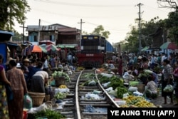 A train makes its way slowly past vendors as they remove their goods from the tracks at the railway bazaar near Tha Ye Zay railway station in Mandalay, Myanmar on May 19, 2019.