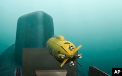 A computer simulation shows a Russian nuclear-powered underwater drone being released by a submarine.
