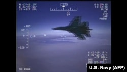 A Russian Su-27 jet is seen in a screenshot from a US Navy video handout flying close to a U.S. reconnaissance plane over the Black Sea on January 29, 2018