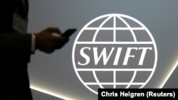 CANADA -- A man using a mobile phone passes the logo of global secure financial messaging services cooperative SWIFT at the SIBOS banking and financial conference in Toronto, Ontario, October 19, 2017