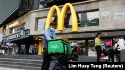 A GrabFood rider gets ready for a delivery outside a McDonald?s restaurant, amid the coronavirus disease (COVID-19) outbreak in Kuala Lumpur, Malaysia July 8, 2020.