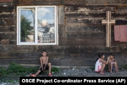 UKRAINE -- Roma children rest in the shade of a church wall inside a Roma encampment on the outskirts of Uzhhorod, June 4, 2018