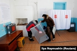 Members of the local electoral commission prepare a ballot box at a polling station in the Siberian village of Verkhniaya Biryusa, March 15, 2018.