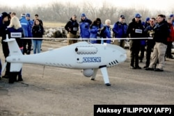 OSCE members for its Special Monitoring Mission stand around a UAV employed in Ukraine.