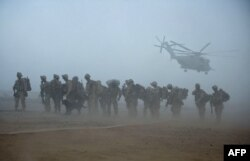 U.S. Marines wait for helicopter transport as part of Operation Khanjar at Camp Dwyer in Helmand Province, 2009.
