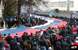Pro-Russian supporters carry a huge Russian flag during a rally in Kharkiv, March 16, 2014