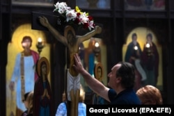 NORTH MACEDONIA -- A man touches the wooden statue of Jesus Christ on a cross at the main Orthodox church St. Kliment in Skopje on Good Friday, April 26, 2019