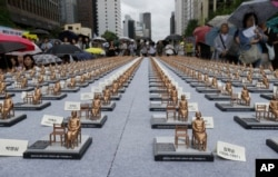 Comfort women statue miniatures are displayed to mark the 5th International Memorial Day for Comfort Women in Seoul, South Korea, Monday, Aug. 14, 2017.