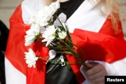 A woman holding flowers and wrapped in the historical white-red-white flag of Belarus attends an action in support of the Belarusian opposition in Warsaw, Poland on September 9, 2020.