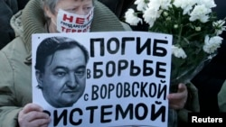 A woman holds a placard with a portrait of Sergei Magnitsky during an unauthorised rally in central Moscow December 15, 2012.
