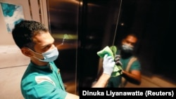 A cleaner wearing a protective mask cleans the elevator doors at the Shangri-La hotel, amid concerns about the spread of the coronavirus disease (COVID-19), in Colombo, Sri Lanka, July 1, 2020.