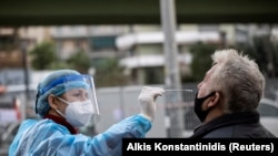 FILE PHOTO: A healthcare worker in personal protective equipment (PPE) takes a swab from a man for a rapid antigen test at a drive-through testing site, during the coronavirus disease (COVID-19) pandemic, in Athens, Greece, Dec. 18, 2020.