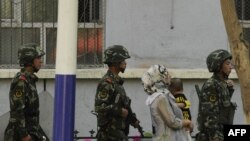 China -- A Chinese paramilatary police patrol passes a Muslim ethnic Uighur woman and a child on a street in Urumqi, capital of China's Xinjiang region on July 3, 2010.