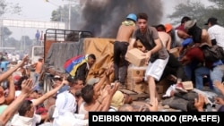 VENEZUELA – People try to take part of the humanitarian aid from a truck that was set on fire in Ureña, Venezuela, on 23 February 2019.
