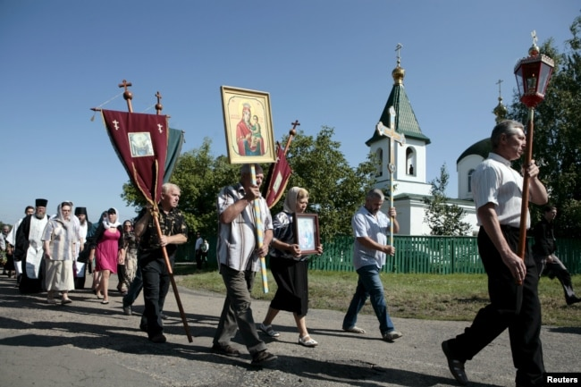 Ukraine -- People take part in a procession to attend a commemoration ceremony near the site of the Malaysia Airlines flight MH17 plane crash in the village of Hrabove in the Donetsk region, July 17, 2015