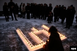 Lithuania -- Commemorating the victims of the Soviet aggression of 13 January 1991, people place lit candles in the shape of the Columns of Gediminas outside the Ministry of Education and Science in Vilnius, January 12, 2017
