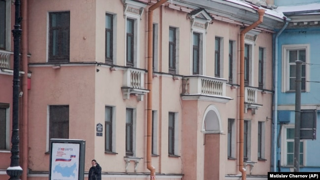 RUSSIA -- A security guard speaks on the phone outside the Concord Catering office in St. Petersburg, February 18, 2018. The company is accused of providing financing for 2016 election interference.