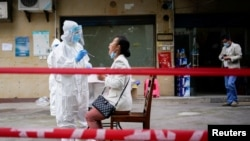 China -- A medical worker in protective suit conducts nucleic acid testings for residents at a residential compound in Wuhan, the Chinese city hit hardest by the coronavirus disease (COVID-19) outbreak, Hubei province, China May 15, 2020.