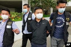 Ryan Law (second from right), Apple Daily's chief editor, is arrested by police officers on June 17, 2021. AP